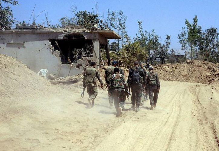 Varios soldados de la armada siria vigilando la zona de Mleiha, en la parte rural de Damasco, Siria. (Agencias)