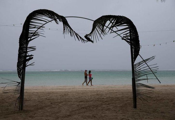 Turistas caminan por la playa Boca Chica al tiempo que comienzan a registrarse las primeras lluvias de la tormenta tropical Erika este 28 de agosto en República Dominicana. (EFE)