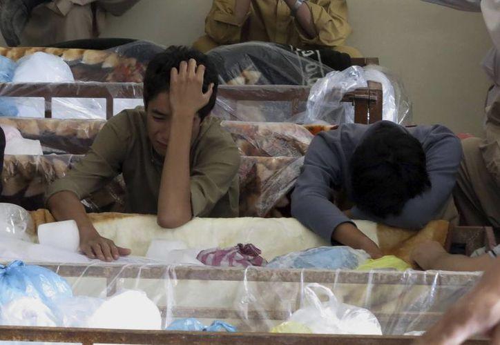 Unos hombres se lamentan ante los cadáveres de musulmanes chiítas, en Quetta, Pakistán. (EFE)