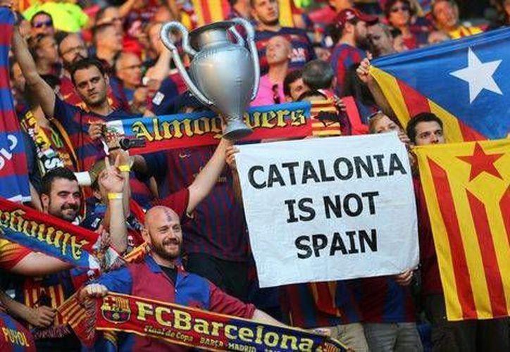 La UEFA sancionó al Barcelona con una multa económica por las pancartas políticas que mostraron los aficionados del equipo español en la última final de la Liga de Campeones, el club deberá pagar 30 mil euros. En la foto: aficionados con las pancartas culpables de la multa al cuadro culé. (AP)