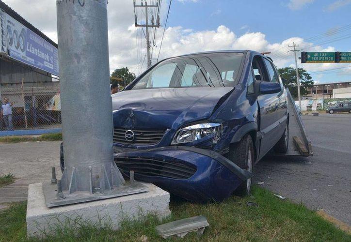 Uno de los vehículos se impactó contra la base del semáforo en la avenida Canek. (Carlos Navarrete)