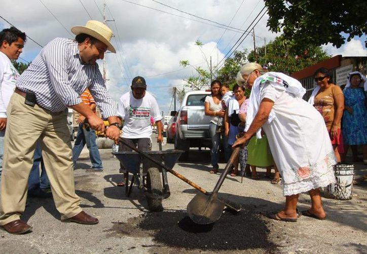 El diputado Francisco Torres Rivas bachea junto con vecinos en la colonia Chuminópolis. (SIPSE)