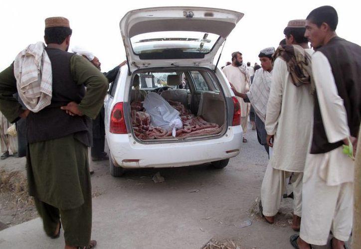 Varias personas se preparan para trasladar el cuerpo de una víctima de un atentado bomba, en la localidad de Lashkar gah, Afganistán. (EFE/Archivo)