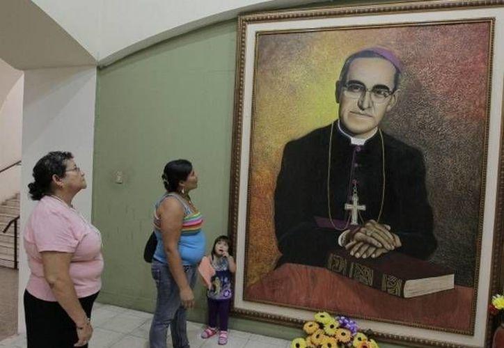 Salvadoreñas observan una pintura del arzobispo asesinado Óscar Arnulfo Romero. (Archivo/EFE)