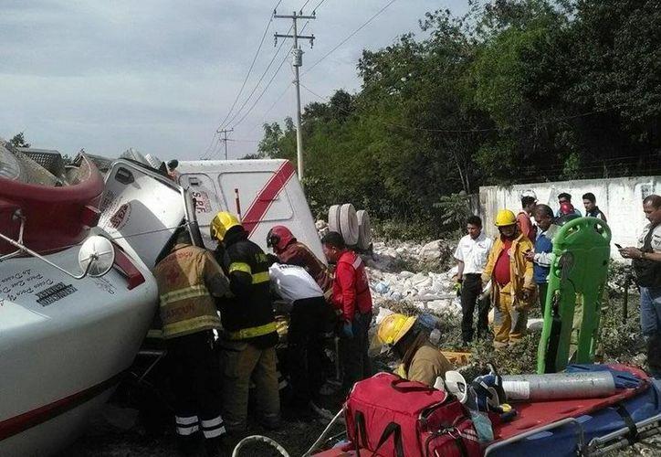 El conductor de la unidad es socorrido por personal de la Cruz Roja y el Heroico Cuerpo de Bomberos. (Sergio Orozco/SIPSE)