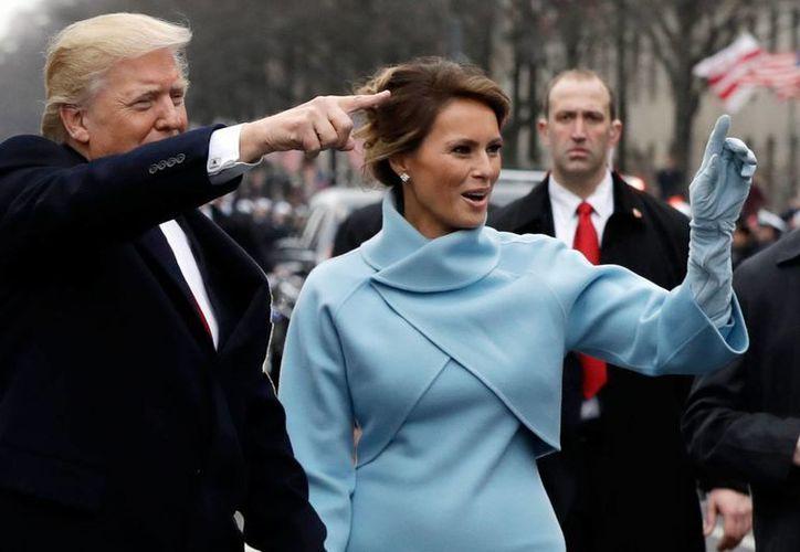 El presidente Donald Trump y su esposa Melania saludan a la gente mientras caminan en la avenida Pennsylvania, tras asumir la Presidencia de EU, el viernes 20 de enero de 2017. (AP/Evan Vucci, Pool)