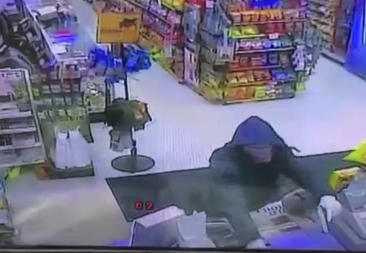El delincuente amenazaba al cajero, sin darse cuenta del otro empleado.  (Captura de pantalla/YouTube)