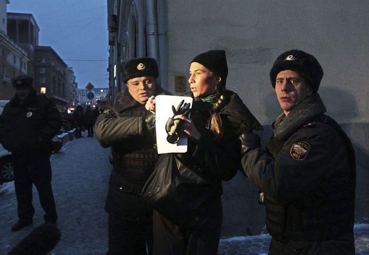 La policía detiene a una mujer que protesta contra de la prohibición de adopción de huérfanos rusos a ciudadanos americanos. (EFE)