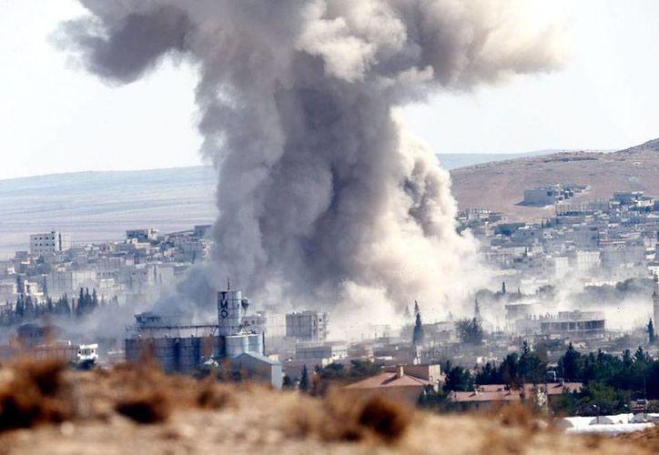 Fotografía tomada desde Turquía que muestra una columna de humo tras un bombardeo aéreo previsiblemente por un avión de la alianza en el oeste de Kobani, Siria. (Efe)