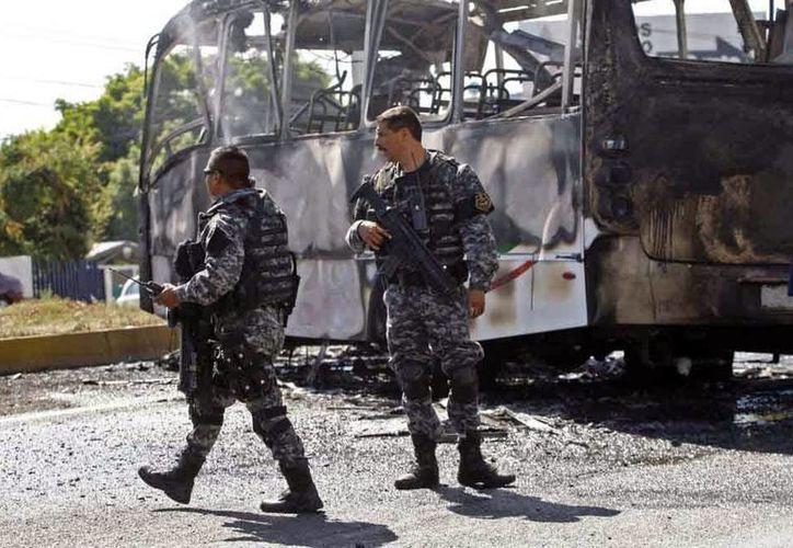 Imagen de dos agentes de la policía estatal junto a un autobús de pasajeros carbonizado, que fue atacado por los criminales, en Guadalajara. (AP)