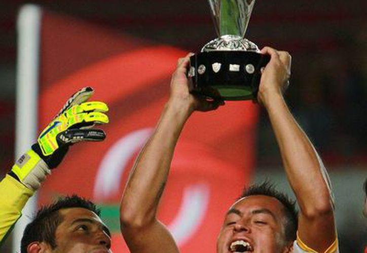 Josue Castillejos (D) del Leones Negros levanta el trofeo de campeón luego del empate con Necaxa, en el juego de vuelta de la final del Torneo Apertura 2013 de la Liga de Ascenso MX. En el partido de ida, el marcador favoreció a a la U de G. (Agencias)