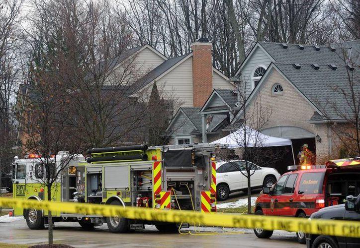 La policía y los bomberos en el lugar de un incendio que mató a cinco personas en una casa en Novi, Michigan, este domingo, 31 de enero de 2016. Las autoridades aseguran que los trabajadores murieron en el fuego que se inició en una casa cerca de Detroit. La causa del incendio está bajo investigación. (Brandy panadero / Detroit News via AP)