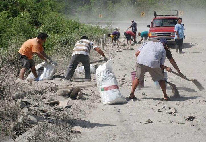 Los habitantes comenzaron a  llegar al sitio para aprovechar llevarse el cemento que permanecía regado sobre el pavimento. (Benjamin Pat/SIPSE)