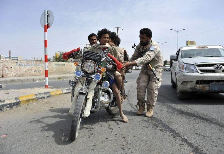 Varios soldados yemeníes inspeccionan una motocicleta en un punto de control en una calle de Saná, Yemen. (Archivo/EFE)
