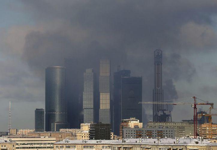Una columna de humo emerge entre varios rascacielos en el nuevo centro financiero de Moscú. (EFE)