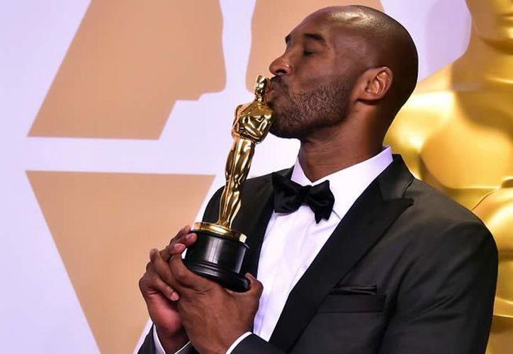 El exjugador de los Lakers besa la estatuilla tras la edición 90 de los Oscars.  (Foto: AFP)