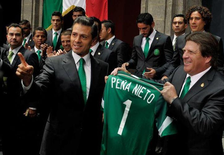 Peña Nieto sostiene la camiseta del Tri con su apellido, junto al entrenador Miguel Herrera, durante el abanderamiento previo al Mundial. (presidencia.gob.mx)