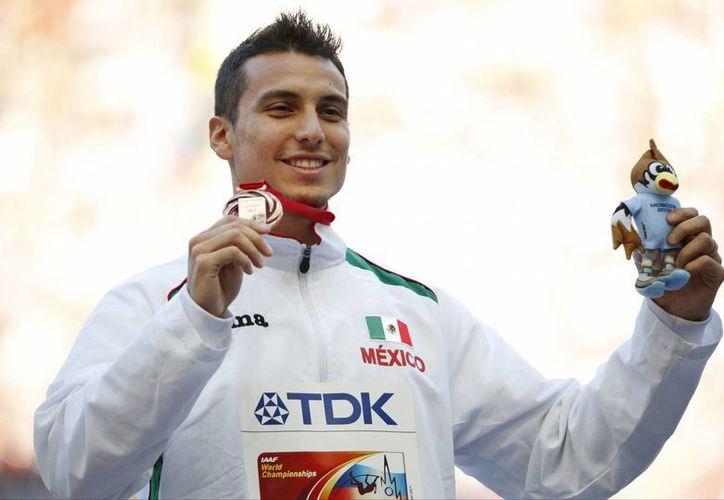 El sonorense Luis Rivera con la medalla de bronce ganada en la prueba de salto de longitud en el CAM. (Agencias)