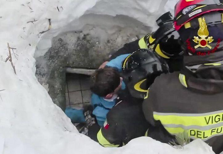Imagen de los bomberos italianos al momento de sacar a un niño vivo de debajo de la nieve y los escombros de un hotel que fue golpeado por una avalancha en Rigopiano. (Bomberos italianos/ANSA vía AP)
