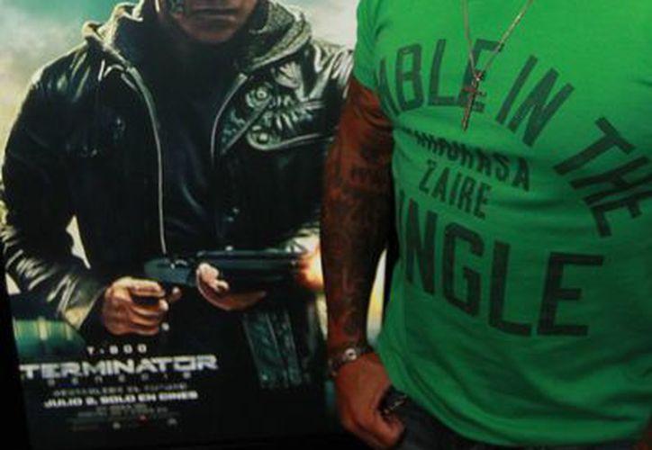 Rey Mysterio dejó la WWE para llegar a la Triple A mexicana, donde espera tener éxito tras salir adelante de varias lesiones. En la foto, junto a un poster de 'Terminator', a quien espera conocer. (Notimex)