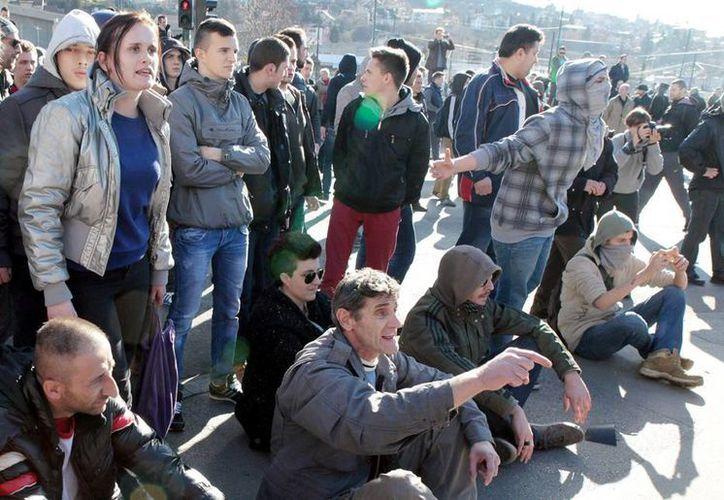 Numerosos manifestantes discuten con miembros de las fuerzas policiales especiales (no aparecen) que hacen guardia durante una manifestación ante la sede del Gobierno cantonal de Sarajevo, Bosnia-Herzegovina. (EFE)