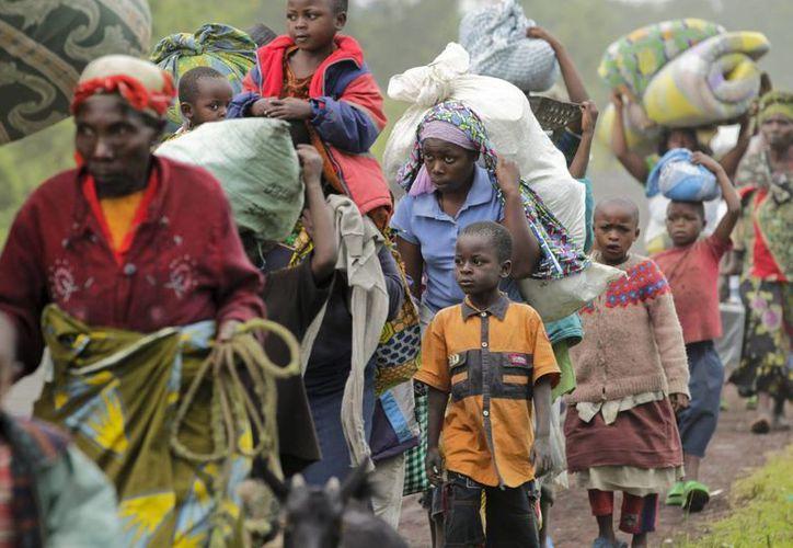 Algunos residentes de Kimbumba escapan de la violencia de su ciudad, en la República Democrática del Congo. (EFE/Archivo)