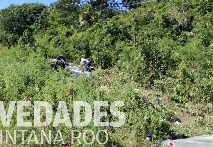 La van de turistas terminó volcada sobre la maleza en la carretera Tulum - Playa del Carmen. (Foto: Sara Cauich)