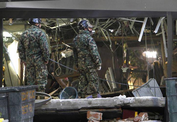 Soldados en medio de los escombros después de la explosión. (Agencias)