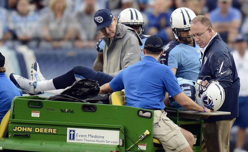 Jake Locker, quarterback de los Titans de Tenesí, es sacado en camilla del partido. (Agencias)