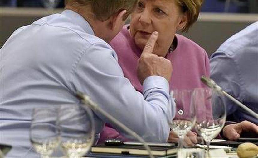 En la imagen, el primer ministro de Irlanda, Enda Kenny (i), dialoga con la canciller alemana, Angela Merkel, durante una mesa redonda en una cumbre de la Unión Europea en Bruselas.(AP)