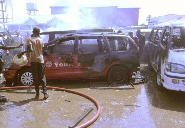 Varios lugareños intentan apagar el incendio causado por la explosión de un artefacto en una estación de autobuses de Gombe, noreste de Nigeria, hoy, viernes 31 de octubre de 2014. (EFE)