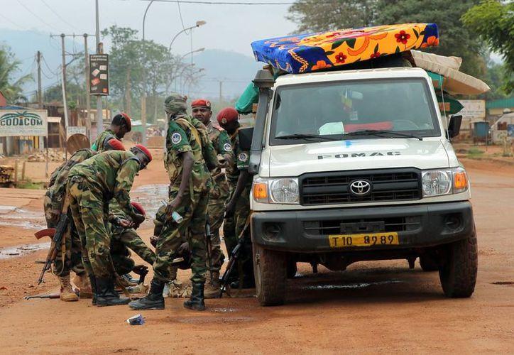 Soldados de las fuerzas FOMAC recargan sus armas en una zona cerca del aeropuerto de Bangui, República Centroafricana. (Agencias)