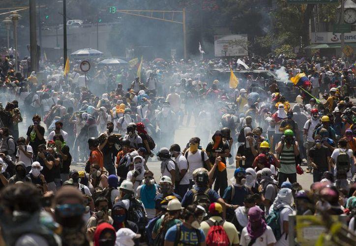 La Policía Nacional Bolivariana tiran gases lacrimógenos a manifestantes antigubernamentales en la Universidad Central de Venezuela, UCV, en Caracas, Venezuela. (Agencias)
