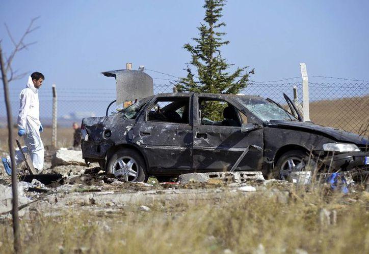 Un forense de la policía de Turquía trabaja en el lugar donde se inmolaron dos suicidas, en Haymana, en las afueras de Ankara, Turquía. (AP)