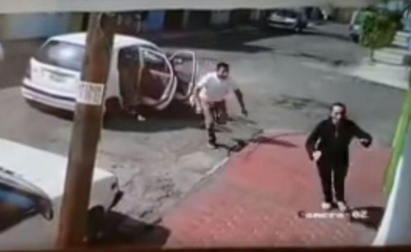 El taxi se estaciona frente a la fémina e inmediatamente bajan dos hombres que corren hacia ella.  (Captura de video)