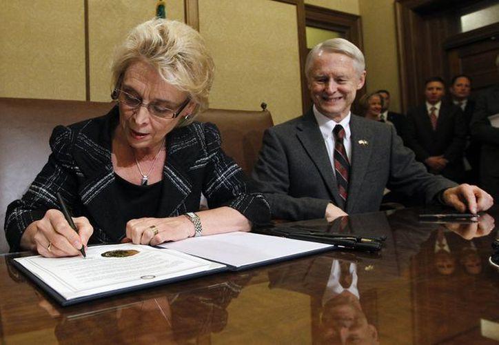 La gobernadora Chris Gregoire firma la certificación de la ley que permite los matrimonios del mismo sexo en Washington. (Agencias)