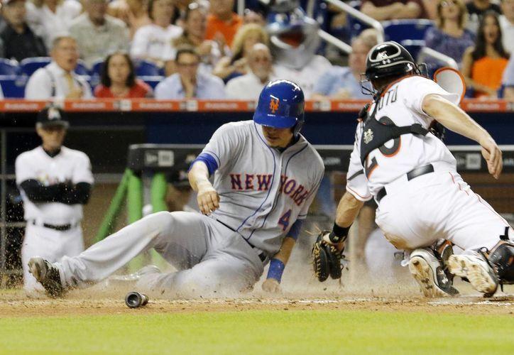 Wilmer Flores, de Mets, anota frente al catcher J.T. Realmuto (20), de Marlins en la quinta entrada del partido ganado por paliza por Mets. (Foto: AP)