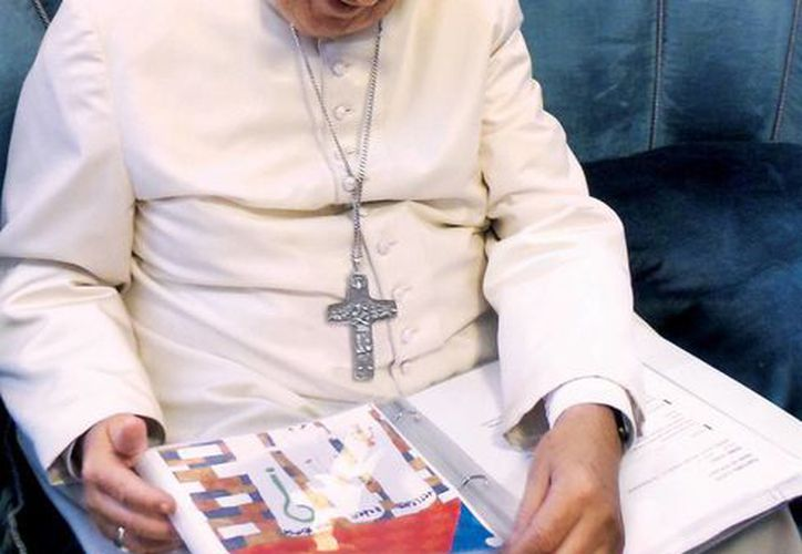 El Papa Francisco observa un cuaderno de preguntas e ilustraciones de los niños de todo el mundo. El Pontífice eligió 30 preguntas y las respondió en el libro 'Querido Papa Francisco', que verá la luz el próximo 1 de marzo de 2016. (Padre Anthony Spadaro, S. J. vía AP)