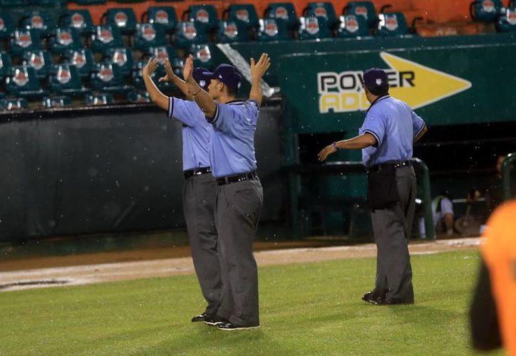 La tercia de ampáyers declara oficialmente la suspensión del juego. (Mauricio Palos/SIPSE)