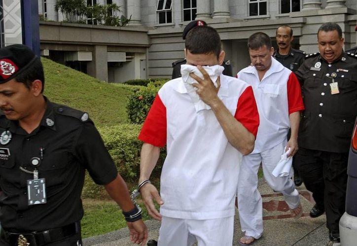 Policías escoltan a los mexicanos José Regino Villareal (centro) y Luis Alfonso González a su salida de una vista en el tribunal de apelaciones de Putrajaya, Malasia. (EFE)