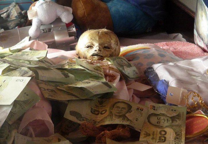 Cadáver de un niño momificado en el templo Mahabut en Bangkok, la capital tailandesa. En ese país, es común que los objetos más exóticos sean venerados. (EFE)