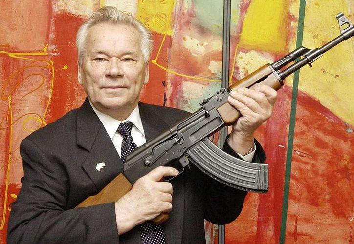 El diseñador de armas ruso Mikhail Kalashnikov con uno de sus rifles de asalto legendario, el AK-47, en Suhl, Alemania, en 2002. (indyweek.com)