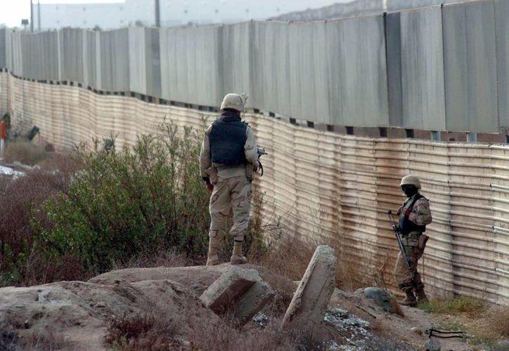 El gobernador de Texas Rick Perry ordenó en julio el despliegue de mil efectivos de la Guardia Nacional en la frontera con México. En la imagen, un par de militares cuida la barda limítrofe. (Archivo/Agencias)