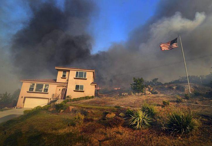 Fotografía facilitada de una columna de humo procedente del incendio que avanza hacia una residencia del condado de San Diego, California. (Archivo/EFE)