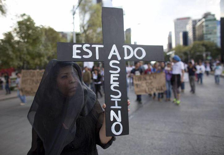 Una mujer con un velo negro desfila como parte de una manifestación en la capital mexicana en exigencia del hallazgo de 43 normalistas de Ayotzinapa, Guerrero. (Foto: AP)