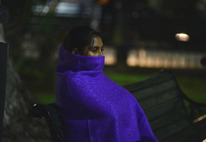 Desde la noche del jueves, los yucatecos salieron a la calle literalmente cubiertos ante la baja drástica en la temperatura. (Luis Pérez/SIPSE)