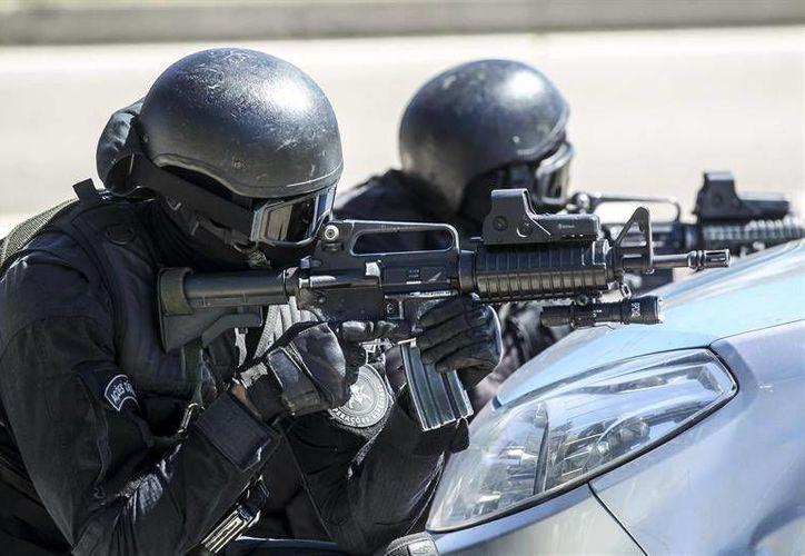 En la foto, miembros de la Policía militarizada de Río de Janeiro realizan un simulacro de rescate de un rehén durante un operativo de preparación para los Juegos Olímpicos de 2016.(EFE)
