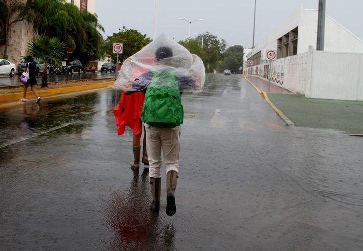Estudiantes y trabajadores salieron este jueves de sus casas preparados para la lluvia.  (María Mauricio/SIPSE)