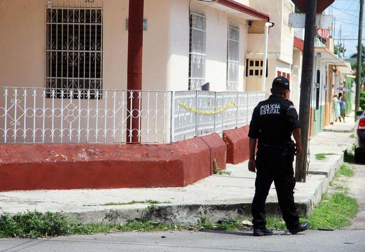 Agentes custodian la casa donde una menor de edad se quitó la vida, en Mérida. La ola de suicidios está imparable en Yucatán: 142 en lo que va de 2016. (Jorge Pallota/SIPSE)