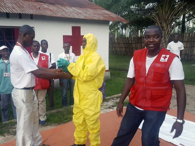 Members of a Red Cross team don protective clothing before heading out to look for suspected victims of Ebola.